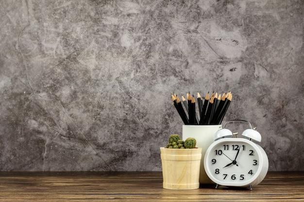 時計、鉛筆、木製の机の上の小さなサボテン