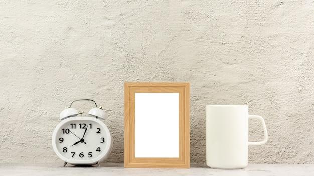 時計と白いコーヒーカップを持つ古典的な木製のフォトフレーム。