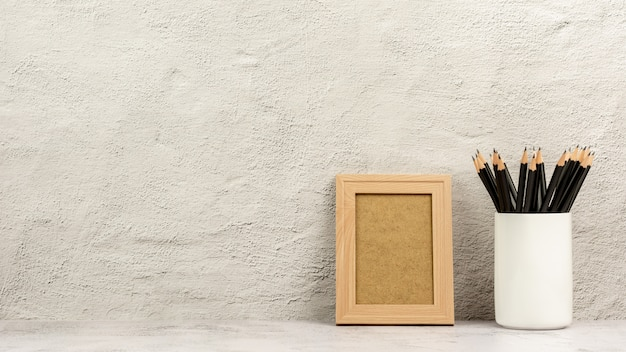 Классическая деревянная фоторамка и множество карандашей в белой чашке