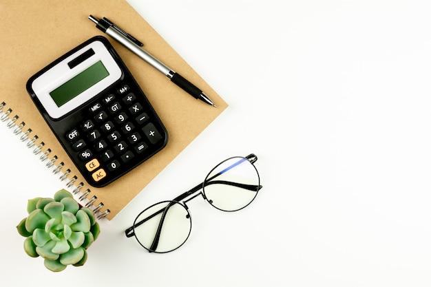 Калькулятор и канцелярские товары на белом столе.