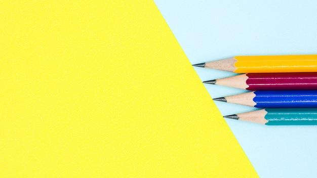 Желтый, красный, синий и зеленый карандаш на синем и желтом фоне