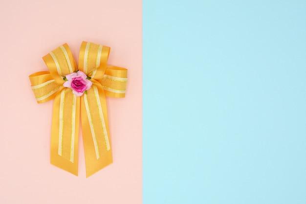ピンクとブルーの背景に高級ゴールドサテンリボン