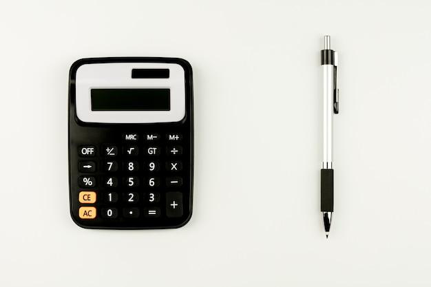 Калькулятор и и ручка на белой таблице. вид сверху с копией пространства.
