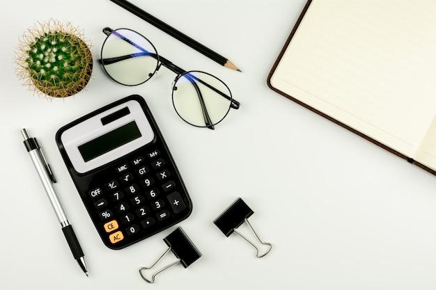 Калькулятор и канцелярские товары на белом столе. вид сверху с копией пространства.