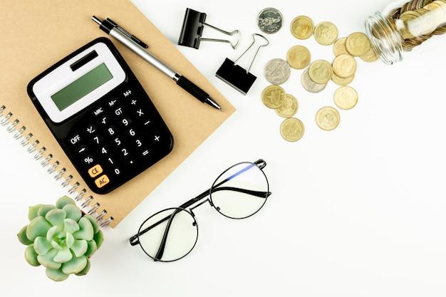 Калькулятор и канцелярские товары на белом столе