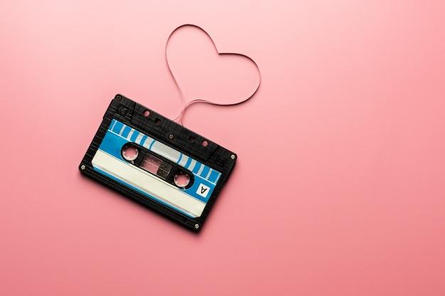 Черная лента кассеты на розовом фоне.