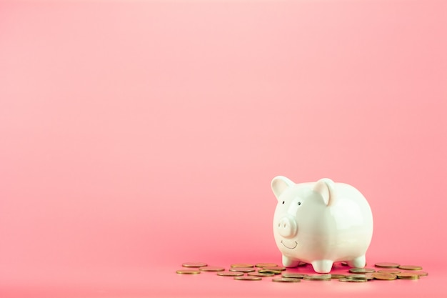 Копилка и куча золотых монеток на розовой предпосылке.