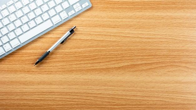 木製の机の背景にペンとコンピューターのキーボード。