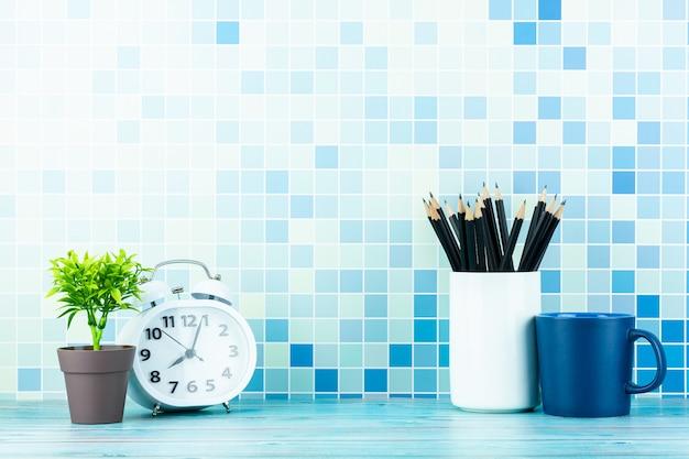 時計、コーヒーカップ、そして青い木製の机の上の鉛筆