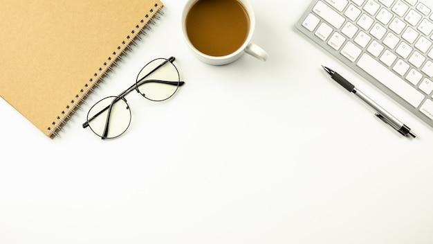 コンピューターのキーボード、ペン、ノート、コーヒーのカップを備えたモダンな白い事務机。