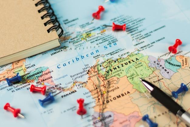 世界地図上のペンと文房具。