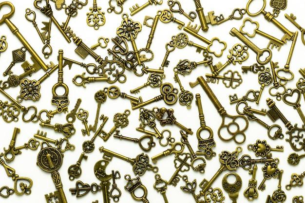 Куча латунных античных ключей изолированных на белой предпосылке.
