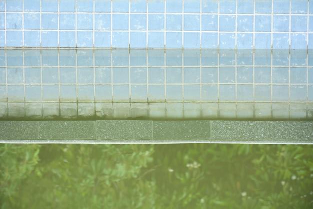 スイミングプールで水の上の反射と抽象的な汚れたタイル