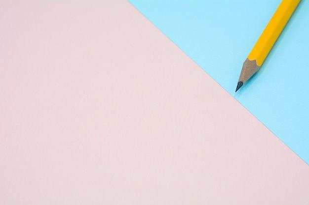 Желтый карандаш на синем и розовом фоне бумаги