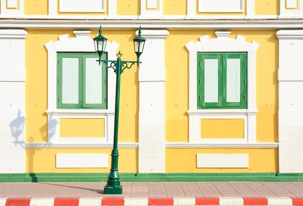 黄色のコンクリートの建物の古典的な木製の窓