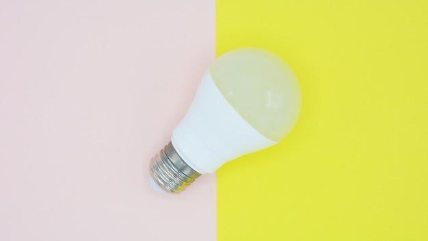 ピンクと黄色の紙の上の電球