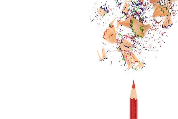 赤い色の鉛筆と白い紙の上に分離されたカラフルな鉛筆の削りくず
