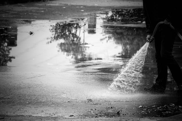 消防士が床に水を噴霧する-モノクロ