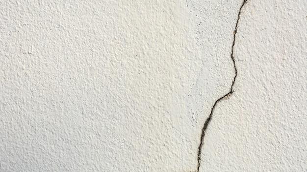 亀裂の白いセメントの壁-背景のテクスチャ