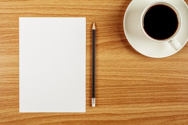 白紙のメモ用紙と木製の机の上の鉛筆