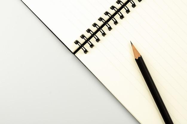日記の本とコピースペースを持つ白いデスク背景に鉛筆