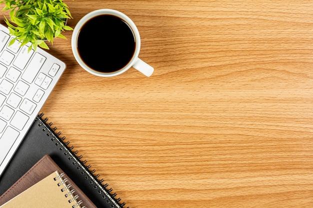 コンピューターのキーボード、木製のオフィスの机の上のノートとコーヒー。 -広告テキスト用の空白スペース。