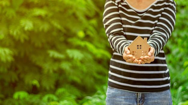 女性の手で小さな家モデル。 -家と不動産の概念を購入します。