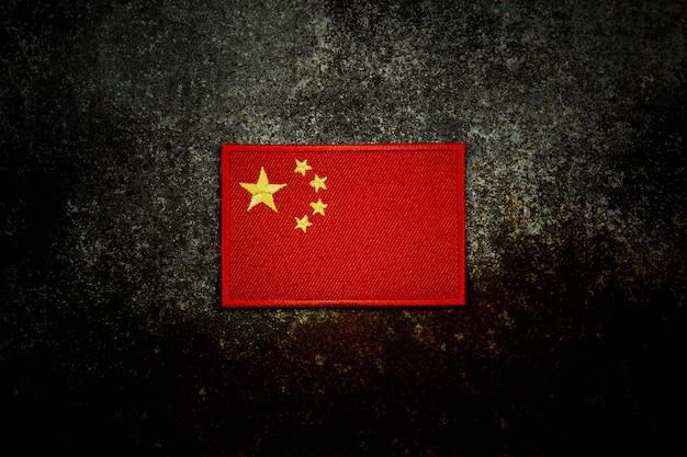 暗闇の中でさびた放棄された金属床の中国の旗。