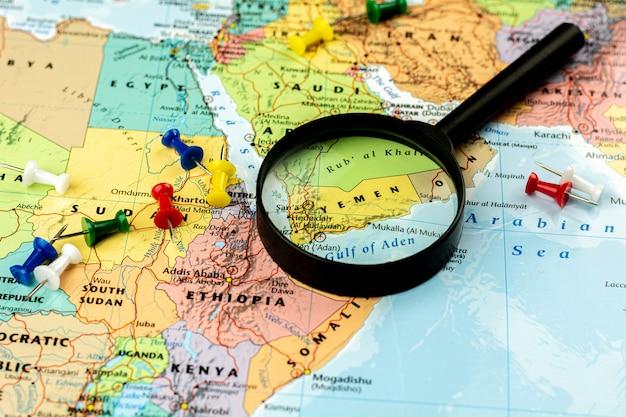 Лупа на карте мира селективный фокус на йемене. экономический и бизнес.
