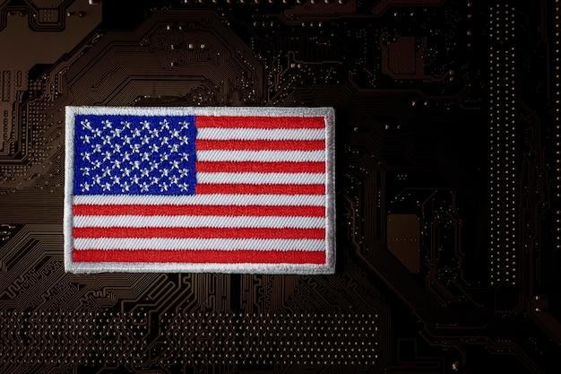 コンピューター回路基板上のアメリカの国旗。セキュリティとサイバー犯罪。