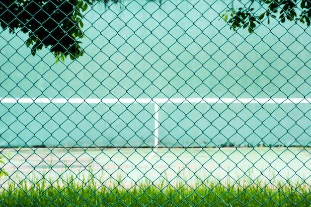 緑の金属製のケージの前に緑のテニスコートと練習用の壁