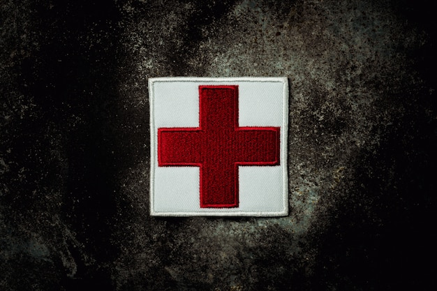 放棄されたさびた金属板に応急処置赤十字フラグ。