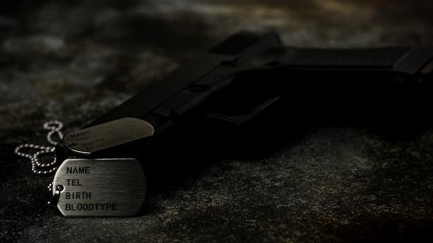 Пустые военные бирки и пистолет на заброшенной ржавой металлической пластине. - концепция воспоминаний и жертв.