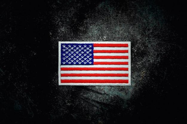 暗闇の中でさびた放棄された金属の床にアメリカの国旗。