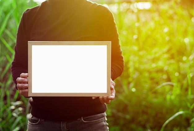 コピースペースを持つ白い空白の広告カードを保持している女性の手。