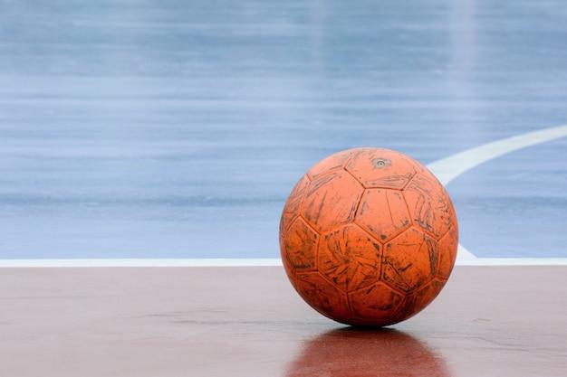 Старый и поврежденный оранжевый мяч на площадке для мини-футбола