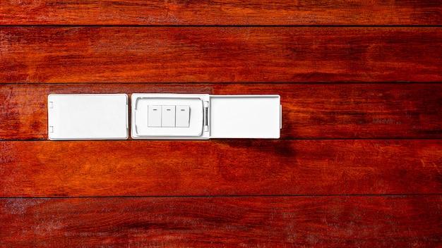 木製の壁にモダンなソケット電気スイッチ。