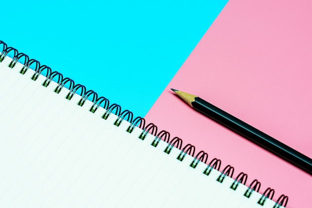 日記の本とコピースペースと青とピンクの背景に鉛筆。 - 上面図。