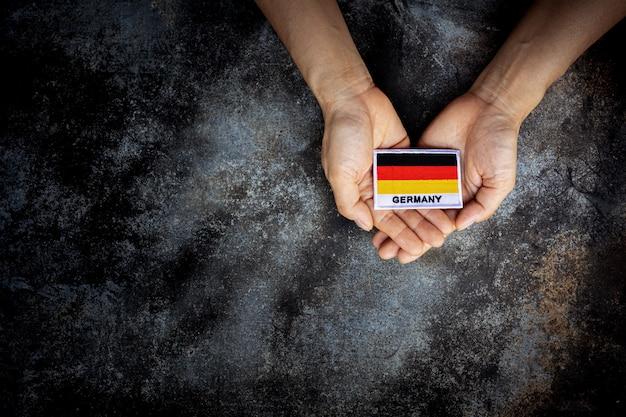 手に小さなドイツの旗。愛、ケア、保護、安全なコンセプト。