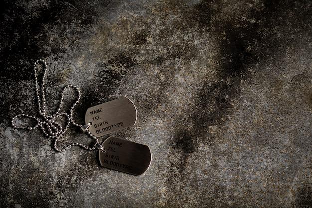 放棄されたさびた金属板に空白の軍事犬タグ。思い出と犠牲のコンセプト。