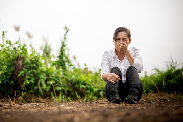 Унылая и плачущая женщина сидит на заброшенной территории.