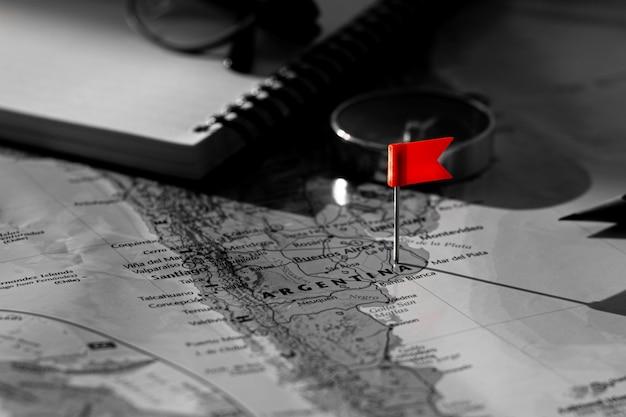 Флаг красного штыря помещенный селективный на карте аргентины. - экономическая и бизнес концепция.
