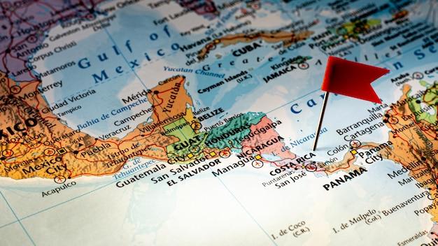 Красный флаг штыря помещенный селективный на карте коста-рика. - экономическая и бизнес концепция.