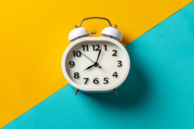 黄色と青の背景に白い目覚まし時計。