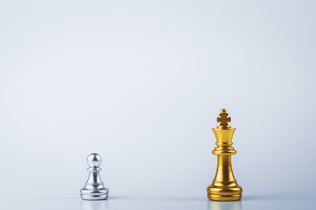 Золотые шахматы короля стоя посреди серебряных шахмат пешки на борту.