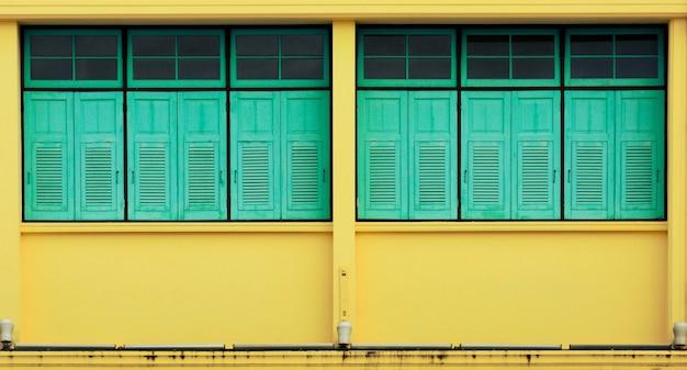 アンティーク黄色のコンクリートの建物で青い窓