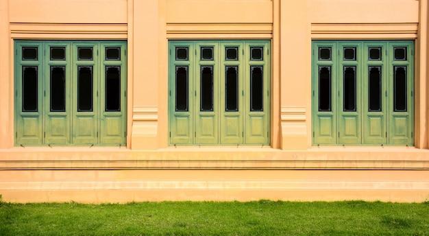 淡いオレンジ色の建物で緑のアンティークの木製窓