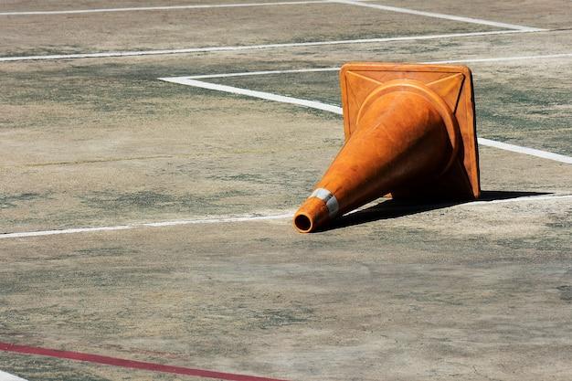 コンクリートの床に横になっているオレンジ色のトラフィックコーン