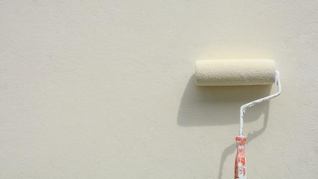 白いセメントの壁にペイントローラー
