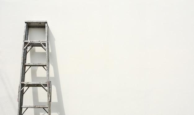 アルミニウム折りたたみ式はしごと白いセメント壁の影